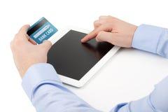 Mans hand som rymmer en kreditkort över en minnestavladator och Royaltyfri Fotografi