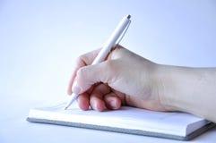 Mans hand som rymmer en penna och skriver i en anteckningsbok royaltyfri bild