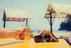 Mans hand som rymmer ett exponeringsglas av öl Royaltyfria Bilder