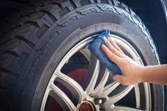 Mans hand som rymmer gummihjul och hjul för en bil för blåtttyglokalvård royaltyfri fotografi