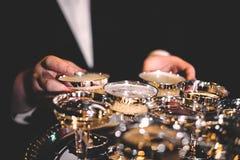 Mans hand som rymmer skinande guld- exponeringsglas av champagne i ett mörkt rum arkivfoto