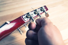 Mans hand tuning a guitar. Vintage colors. Royalty Free Stock Images
