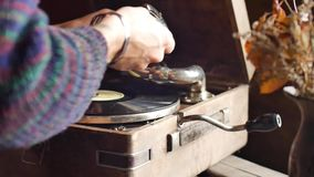 Mans hand turning the handle of the old retro gramophone close-up slow motion shot stock video