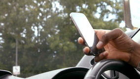 Mans hand using smartphone. In car stock footage
