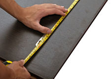 Mans hand using tape measure. Mans hand using yellow tape measure on dark wooden panel Royalty Free Stock Photos