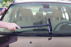 Mans hand washing windshield of car at gas station-GPS sitting on dash royalty free stock photo