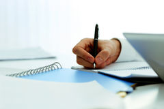 Mans hand writing in notebook Royalty Free Stock Image