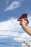 Mans handen som rymmer hans pass som ett pappers- flygplan över en tagg Royaltyfri Foto