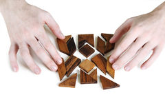 Mans hands assembling wooden square puzzle Royalty Free Stock Photos