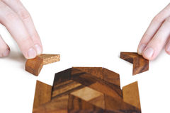 Mans hands assembling wooden square puzzle Stock Photo