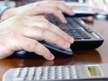 Mans hands on computer mouse and keyboard Stock Photos