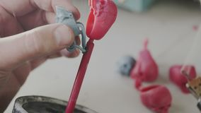 Mans hands create wax molds of skull ring for production of jewelry. Goldsmith in work. Soldering tool for melt waxy