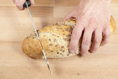 Mans hands cutting a loaf sunflower seeded bread stock photography
