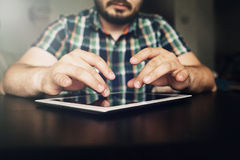 Mans hands fingers on tablet on table. Close up view stock image