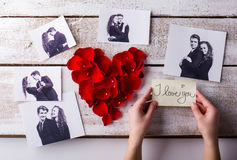 Mans hands. His and his girlfriends photo. Rose petal heart. Stock Images