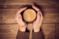 Mans hands holding a cup of coffee with foam over wooden table, Stock Photo