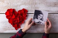 Mans hands holding his girlfriends photo. Red rose petal heart. Stock Images