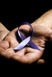 Mans hands holding purple domestic violence awareness ribbon. Healthcare and social problems concept - mans hands holding purple domestic violence awareness Royalty Free Stock Images