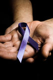 Mans hands holding purple domestic violence awareness ribbon. Healthcare and social problems concept - mans hands holding purple domestic violence awareness Royalty Free Stock Photos
