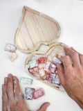 Mans hands placing turkish delight in a heart shaped box Stock Photos