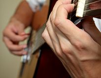 Mans' hands playing guitar Stock Images