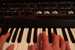 Mans hands playing a vintage retro analogue synth.  Royalty Free Stock Photos
