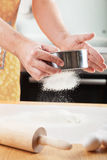 Mans hands sifting flour through a sieve for baking Royalty Free Stock Image