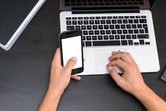 Mans hands typing on smart phone while working on laptop compute stock image