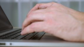 Mans hands typing text at laptop keyboard. Extreme close up fingers type text on keyboard. CU stock video footage