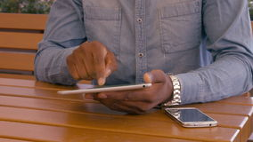 Mans hands using tablet. Outdoors stock footage