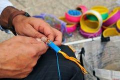 Mans hands weaving a bracelet. Royalty Free Stock Photo