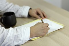 The mans hands on white medical outfit writes with roller pen on the paper on wooden table. The cup of tea of coffee on the table. stock photos