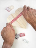 Mans hands wrapping  a  heart shaped gift box with a ribbon Royalty Free Stock Photo
