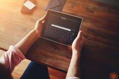 Mans händer genom att använda en digital iPadminnestavla på kontoret Fotografering för Bildbyråer