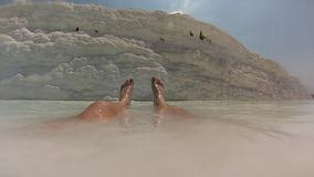 Mans lags in calcium bath, Pamukkale. Turkey stock video footage
