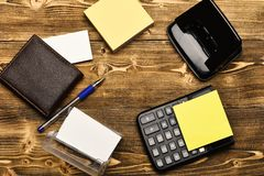 Mans leather wallet and stationery organized in circle. Mans leather wallet and stationery. Calculator, hole punch, card holder, note paper and pen organized in royalty free stock photo