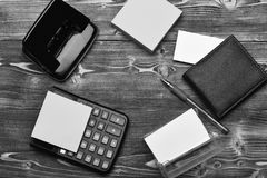 Mans leather wallet and stationery organized in circle. Mans leather wallet and stationery. Calculator, hole punch, card holder, note paper and pen organized in stock photos