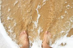 Mans leg standing on the sand and lapped by the o. Top view of a mans leg standing on the sand and lapped by the ocean waves stock photos
