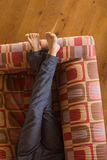 Mans legs on the couch Stock Photos