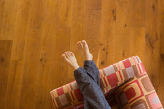 Mans legs on the couch Stock Images