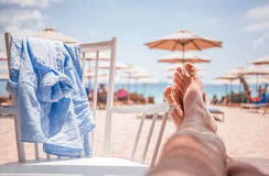 Mans legs stretch out on the beach Stock Photo
