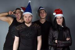 Mans metallmusikband med röda och blåa julhattar royaltyfri bild