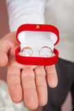 Mans palms holding wedding rings in red box Royalty Free Stock Photo