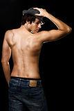 Mans profile. Handsome young shirtless brunette man wearing hat showing bare back standing in profile with hand on head stock image