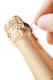 Mans räcker uncorks en champagne buteljerar Royaltyfri Fotografi