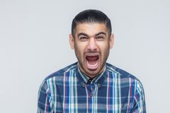 Mans roar! The angry businessman, screaming with closed eyes. Indoor, studio shot.  Gray background Stock Images