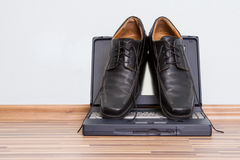 Mans shoes on the notebook Stock Photography