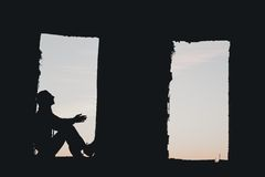 Mans silhouette in the window above blue cloudy Stock Photography