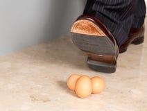 Mans sko som stämplar på tre ägg Arkivbilder