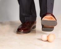 Mans sko som stämplar på tre ägg Royaltyfri Fotografi